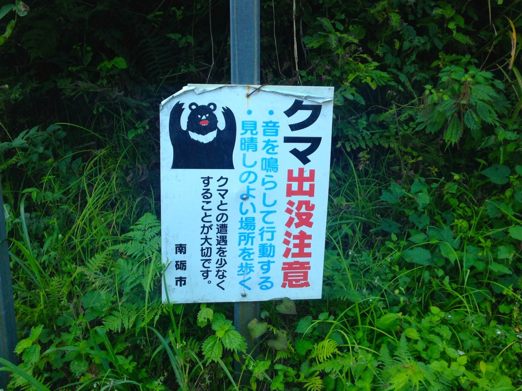 Warning sign for bears in Japanese forest.