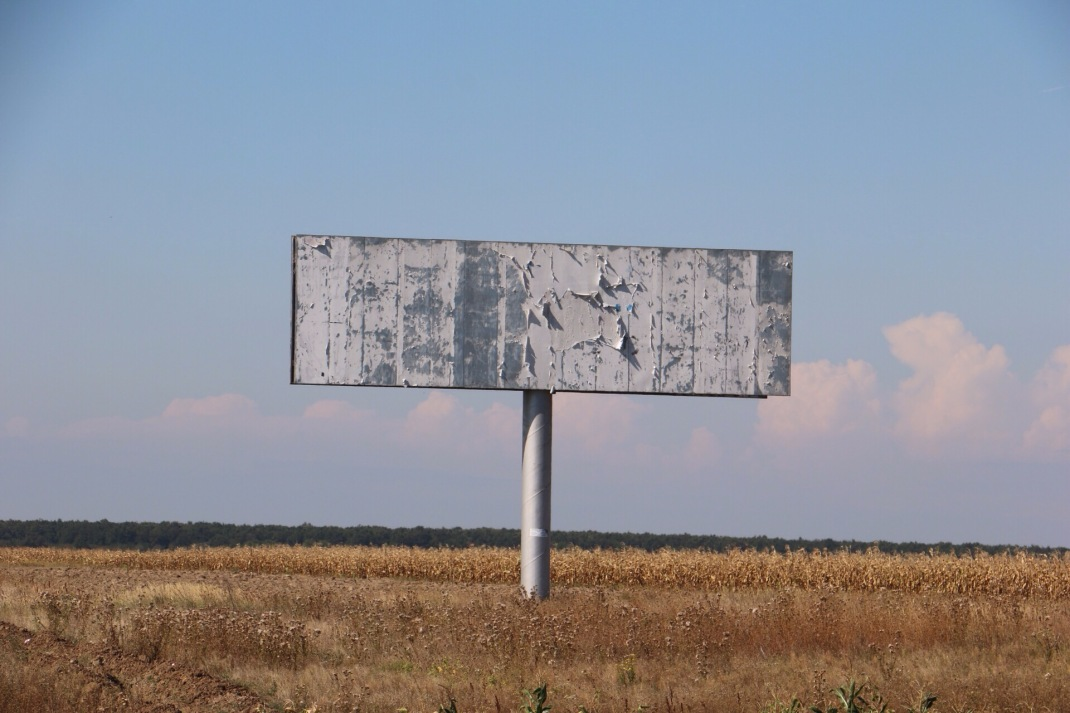 Romania empty billboard in front of corn fields. Crank and Cog cycle tour of Romania.