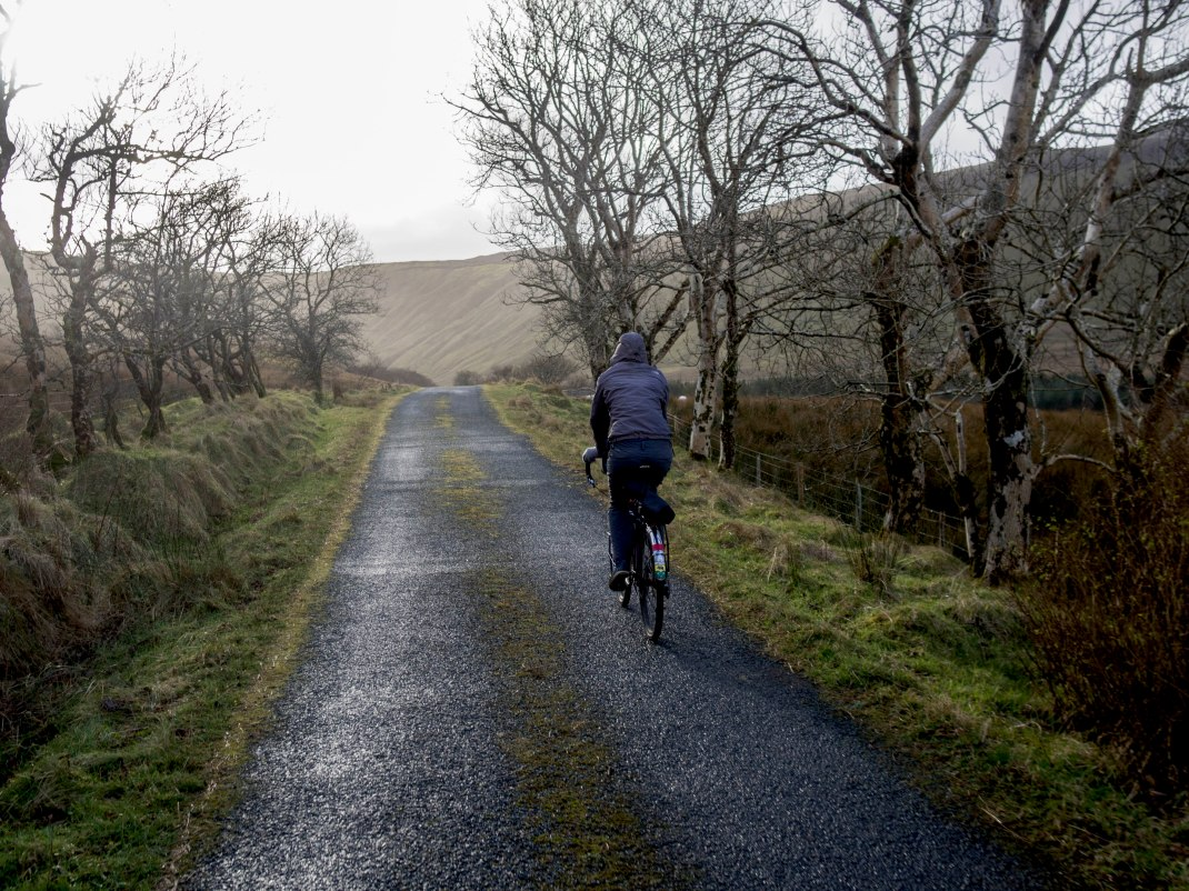 Laura cycling a green ridged road at Gleniff, County Sligo, Ireland | Crank and Cog one day cycle loops in Ireland. Local Loops.